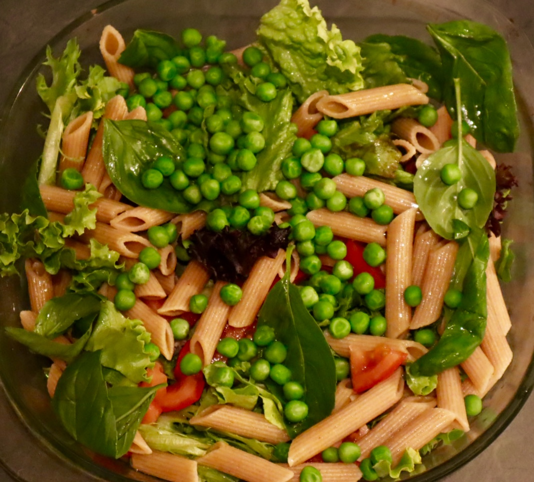 Whole Wheat pasta salad with tomato, basil, peas and garlic